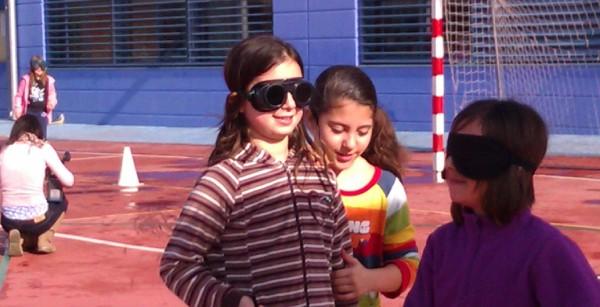 Una niña ayuda a otra que simula tener una cegera
